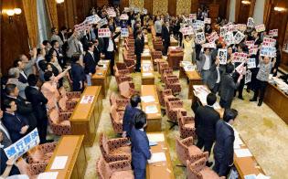 15日、野党議員が抗議する中、自民、公明両党の賛成で安全保障関連法案を可決した衆院平和安全法制特別委=共同