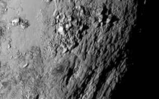 冥王星の表面には氷でできた山脈が連なり、クレーターが見られない(NASA/JHU APL/SwRI)