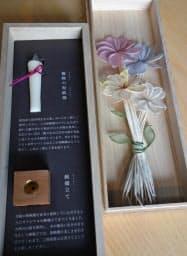 桐箱に収められている筒井時正玩具花火製造所の「花々」。ハゼの実から抽出されたロウでできた和ろうそくと、九州の山桜でつくったとろうそく立てもセットになっている