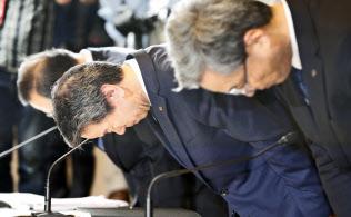 記者会見で頭を下げる東芝の田中久雄社長(中、7月21日、東京都港区)