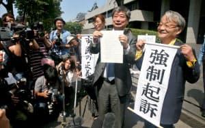 東電元会長らの強制起訴が決まり、垂れ幕を手にする告訴団(31日午後、東京・霞が関)