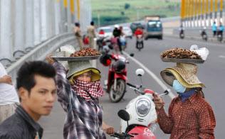 日本の援助で開通した「つばさ橋」。メコン川の上を人々が行き交う(カンボジア)=写真 小川望