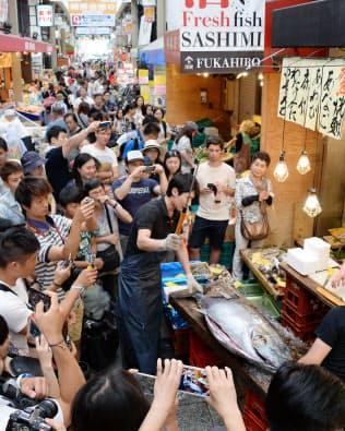 黒門市場でマグロの解体に見入る外国人観光客ら(12日、大阪市中央区)
