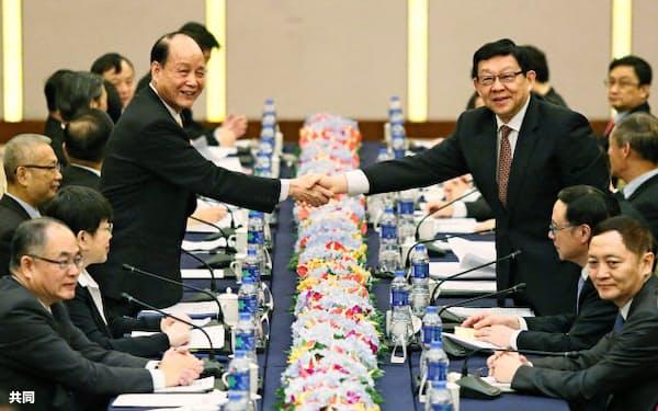 25日、会談前に握手を交わす台湾の林中森・海峡交流基金会理事長(左)と中国の陳徳銘・海峡両岸関係協会会長=中央通信社・共同