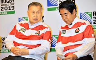 ラグビーW杯日本大会開催に暗雲が広がっている(7月15日、「キックオフミーティング」で下村文科相(右)と話す森元首相)=共同