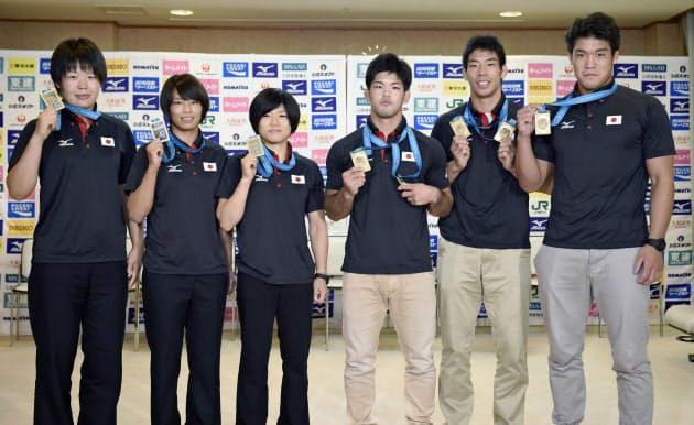 金メダルを掲げる、柔道日本代表の(左から)梅木真美、松本薫、中村美里、大野将平、永瀬貴規、羽賀龍之介の各選手(1日、成田空港)=共同