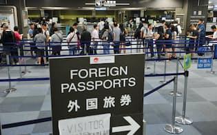 法務省が外国人在留資格を拡大を検討。成田空港の入国審査ゲートに並ぶ外国人旅客
