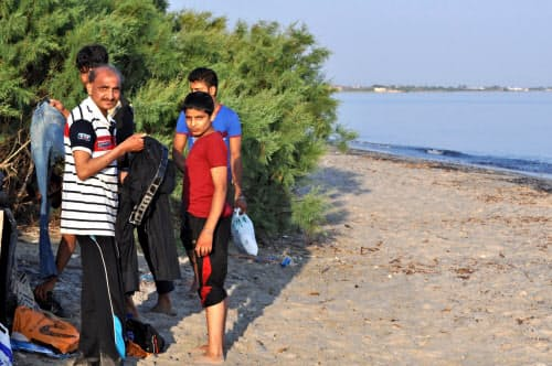 ギリシャ・コス島に上陸し、ぬれた衣服を着替えるパキスタン人の一団