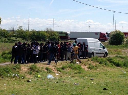 仏カレーで慈善団体からの食事の提供を受ける移民たち