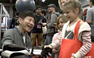 イクシーが開発した電動義手を装着し、イベント会場で来場者と握手する森川章氏