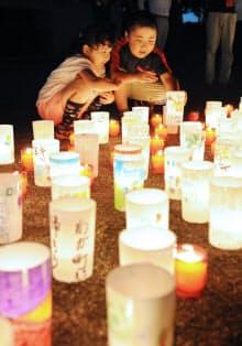 避難指示解除を前に開かれたイベントでキャンドルを並べる子どもたち(4日、福島県楢葉町)