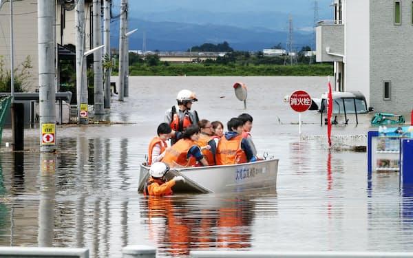 渋井川(奥)の堤防が決壊し、浸水した住宅地からボートで救助される住民ら(11日午前、宮城県大崎市)