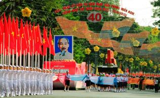 ベトナムで「建国の父」とされる故ホー・チ・ミン氏の肖像画とともに行進する兵士ら(ホーチミン市)