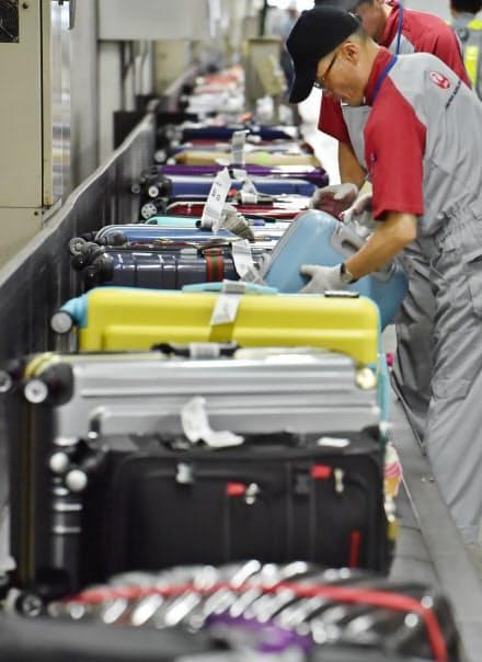 乗客が取りやすいようにスーツケースの持ち手は外側に向ける