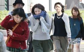 冷たい風が吹く中、身を縮めて歩く人たち(25日午前、東京・有楽町)