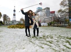 うっすらと雪が積もった札幌・大通公園で記念写真を撮る観光客(25日)=共同
