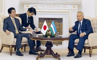 ウズベキスタンのカリモフ大統領(右)と会談する安倍首相(25日、タシケント郊外)=共同