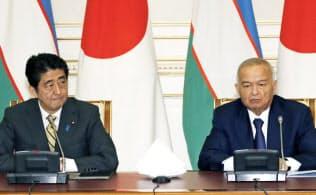 ウズベキスタンのカリモフ大統領と共同記者発表を行う安倍首相=25日、タシケント郊外(共同)