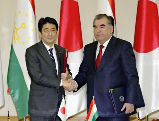 共同声明の覚書を交換し、ラフモン大統領(右)と握手する安倍首相(24日、タジキスタン・ドゥシャンベ)=共同