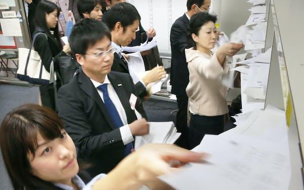 決算発表の資料を棚に入れる企業の担当者ら(10月30日午後、東証)