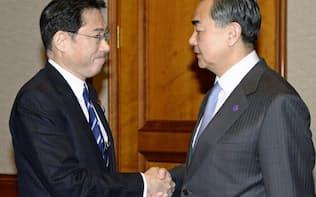 会談を前に握手を交わす岸田外相(左)と中国の王毅外相=1日、ソウル(共同)