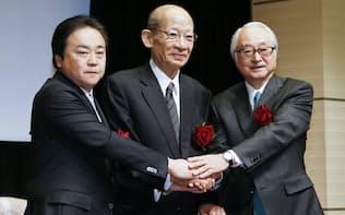 日本郵政グループ3社が上場し、握手する(右から)ゆうちょ銀行の長門社長、日本郵政の西室社長、かんぽ生命の石井社長(4日午前、東証)