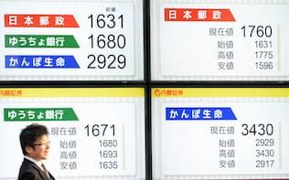 日本郵政グループ3社の初値(左上)と各社の終値を示す電光掲示板(4日午後、東京都中央区)