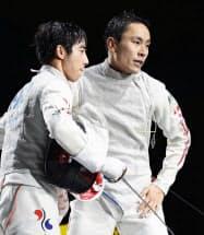 男子フルーレ個人準決勝で韓国の許俊(左)に敗れ引き揚げる太田雄貴(7日、駒沢体育館)=共同