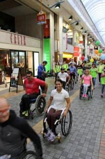 大分市の商店街のアーケードをパレードする車いすマラソンの選手たち
