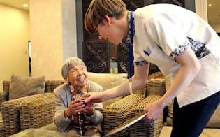 お年寄りにお茶を出すドイツ人インターンのミショックさん(尼崎市の特別養護老人ホーム「アマルネス・ガーデン」)