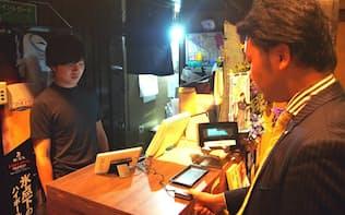 居酒屋「和食Dining 黒田」(東京都新宿区)での生体認証決済の様子。センサーに指を押しつけるだけで決済が完了する。30歳前後男性の利用が多いという