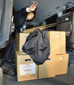 強制調査で村上元代表の関係先から運び出された押収物(25日、東京都港区)