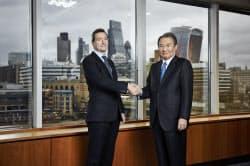 日経の喜多会長(右)とFTのリディングCEOは握手を交わした(30日、ロンドン)