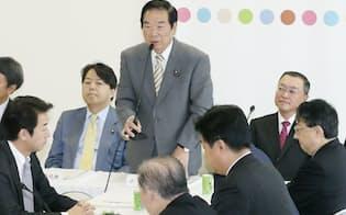 自民党税調総会・小委員会であいさつする額賀小委員長。右は宮沢会長(10日午前、自民党本部)