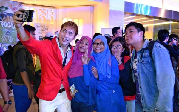インドネシアのファンと記念撮影するアキラ・コンチネンタル・フィーバーさん(左)