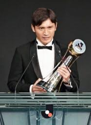Jリーグの年間表彰式で、最優秀選手賞のトロフィーを手にあいさつする広島・青山敏弘(21日、東京都内のホテル)=共同