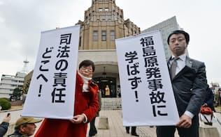 高浜原発再稼働を認める判断が出され、垂れ幕を掲げる弁護士ら(24日午後、福井地裁前)