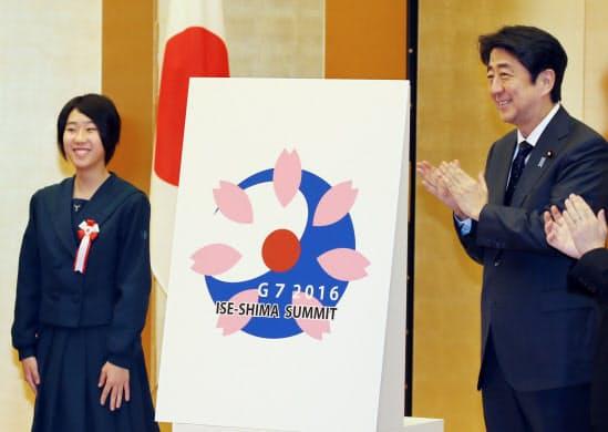 披露された伊勢志摩サミットのロゴマーク。左は制作者の宇津宮志歩さん(15年12月28日、首相官邸)
