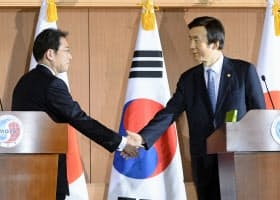 共同記者発表を終え、握手する岸田外相(左)と韓国の尹炳世外相(28日、ソウルの韓国外務省)=共同