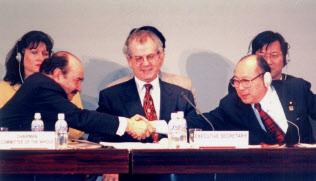 本会議終了後、エストラーダ議長(左)と握手する大木浩京都会議議長(97年12月)