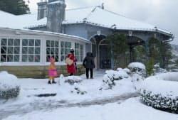 雪が積もった世界文化遺産の旧グラバー住宅と観光客(24日午後、長崎市)=共同