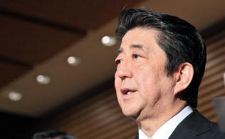 甘利経財相が辞任を表明し、記者の質問に応じる安倍首相(28日午後、首相官邸)