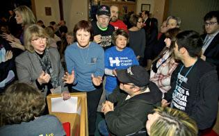 1日、米アイオワ州デモインの教会で開かれた民主党の党員集会で、どの候補者を選ぶべきかを議論する参加者(共同)