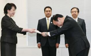 高市総務相(左)からスマートフォンの料金や端末販売についての要請書を受け取るNTTドコモの加藤社長(昨年12月18日)