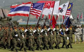 開会式で入場行進する多国間軍事演習「コブラゴールド」の主要参加国の国旗を掲げた兵士(9日、サタヒープ・タイ)=写真 沢井慎也