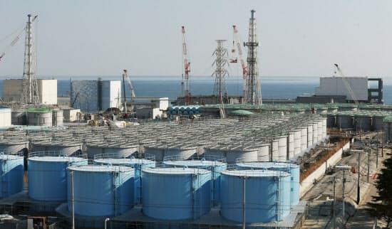 福島第1原発構内に並ぶ処理済みの汚染水をためたタンク(手前)。奥には(右から)4号機、3号機(鉄塔の左)、2号機、1号機が廃炉を待つ(9日、福島県大熊町)