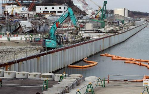 鋼管を並べた遮水壁で地下水の流出を防ぐ。左奥は津波の被害を受けた施設(福島県大熊町)