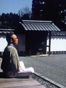 寺の縁側で思索する谷村さん=所属事務所のダオ提供