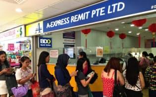 週末には故郷への送金のため出稼ぎフィリピン人の長い行列ができる(シンガポール繁華街の商業ビル、ラッキー・プラザ)