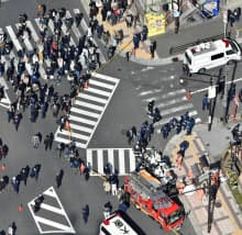大阪・梅田で乗用車が暴走したスクランブル交差点。事故直後も多くの人が行き交う=25日午後1時7分(共同通信社ヘリから)